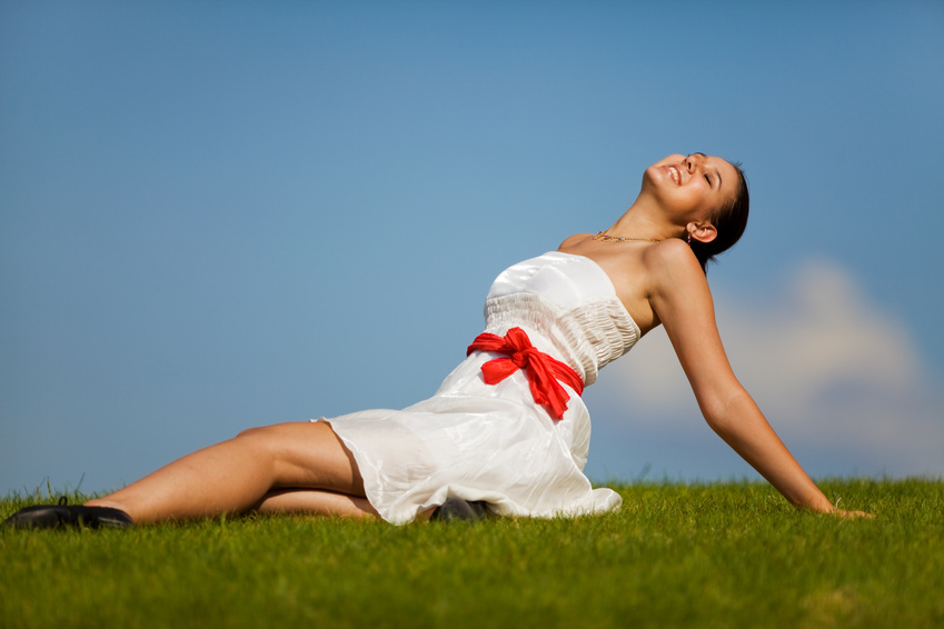 woman in a white dress with red ribbon sitting on grass with arms back